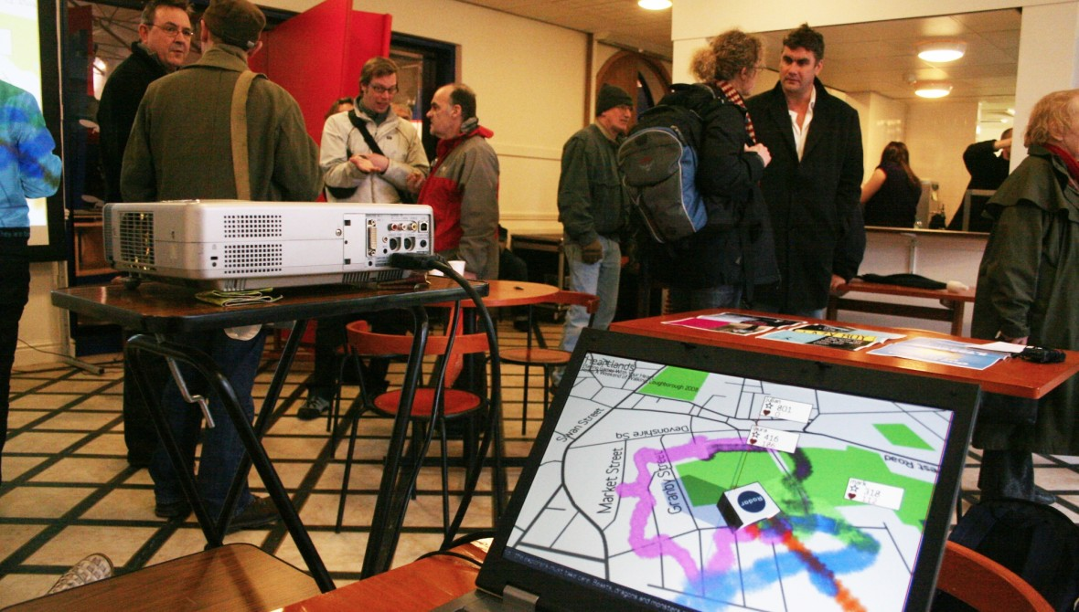 People milling about in a room. There is a laptop open on a table, which shows a map overmaked with pink, blue and orange tracks showing where people have walked.
