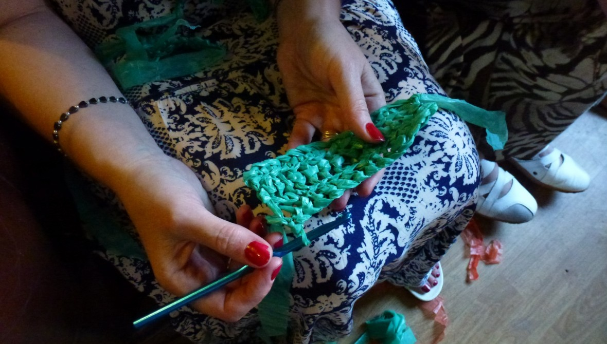 A person crochets with plastic.